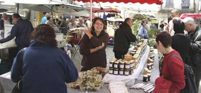 Nadia, apicultrice, propose à la vente ses produits à base de miel sur un marché de la drome